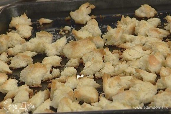 Приготовить крутоны: срезать с хлеба корку, поломать его на небольшие кусочки, сбрызнуть оливковым маслом и запекать в духовке 7–8 минут.