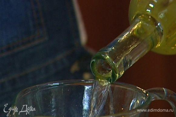 В большой кувшин выложить немного льда и влить вино.