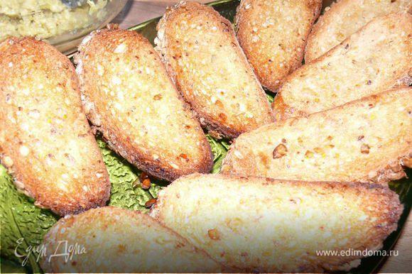 Порезать багет тонко наискосок, сбрызнуть ломтики оливковым маслом, поставить запекать в духовку на сухом противне 10-15 минут.180 градусов до золотистого цвета.Готовые теплые ломтики натереть долькой чеснока.