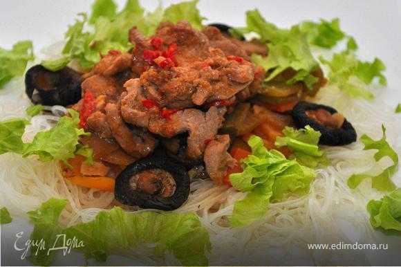 Собираем блюдо. На тарелку выложить лапшу, поверх тушеные овощи и соус , затем кусочки мяса. Украсить блюдо можно листьями салата или китайской капусты.