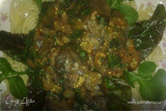На блюдо выложить макароны, затем разложить листья рукколы и мангольда и сверху в середину выложить тушеные баклажаны.