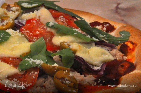 Отправить пиццу обратно в духовку еще на 5-6 мин. Готовую пиццу вынуть из духовки, немедленно посыпать свежей рукколой и крошкой пармезана, слегка сбрызнуть оливковым маслом, поперчить и подать к столу.