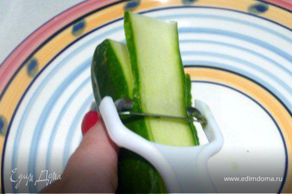 Огурцы нарезать овощечисткой полосками. Но не захватывать семена. Поставить нарезанные огурцы в холодильник на 10 минут.