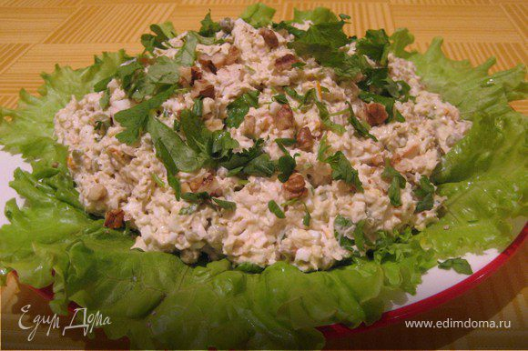 Листья салата разложить на тарелку, на них выложить салат, посыпать петрушкой и орехами.
