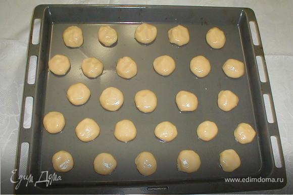 Десертной ложкой вложить тесто на противень с расстоянием между шариками 3 см. Впекать следует 20-25 минут в прогретой духовке. Через 10 минут после начала выпечки, когда шарики поднимутся и зарумянятся, уменьшить огонь и выпекать ещё 10 минут до полной готовности.