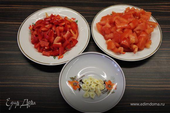 Тем временем нарезаем овощи кубиками и чеснок колесиками. На сковороду с разогретым маслом кидаем помидоры и томим, пока совсем не растают. Добавляем чеснок со сладким перцем и держим до готовности. Посолить.