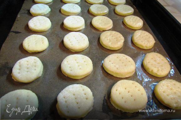 Противень застелить пергаментом, смазанным растительный маслом, выложить печенье, каждое проколоть вилкой.