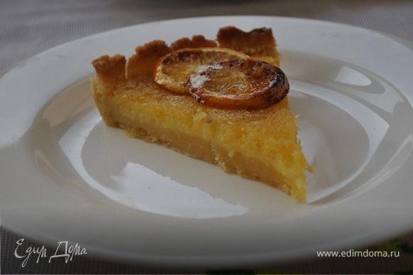 Вылить начинку на подготовленное тесто и выпекать 15-20 минут. Остудить на решетке. Украсить пирог можно карамелизированными лимонными дольками. Для этого нужно нарезать тонко лимон, каждую дольку обвалять в сахарной пудре и запечь под грилем до румяного цвета.