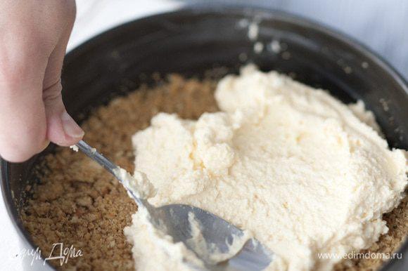 Смазать разъемную форму для выпечки оставшимся сливочным маслом. Выложить сначала массу из крошек, а сверху — творожную массу.