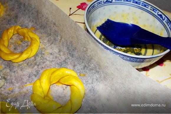 Выкладываем наши готовые печенья на застеленный бумагой для выпечки противень и смазываем желтком.