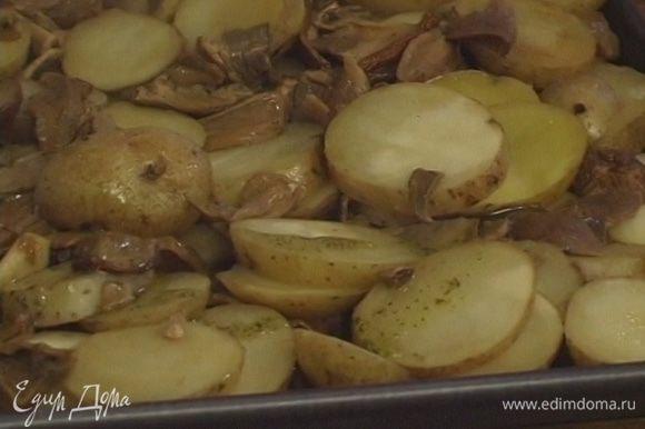 Смазать дно противня половиной заправки, выложить картошку с грибами, полить оставшейся заправкой.