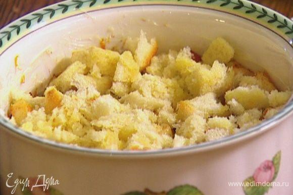 Керамическую форму смазать сливочным маслом, выложить в нее большую часть хлебных кусочков и слегка утрамбовать, сверху разложить половину яблок с клюквой, затем опять слой хлеба и на него — оставшиеся яблоки.