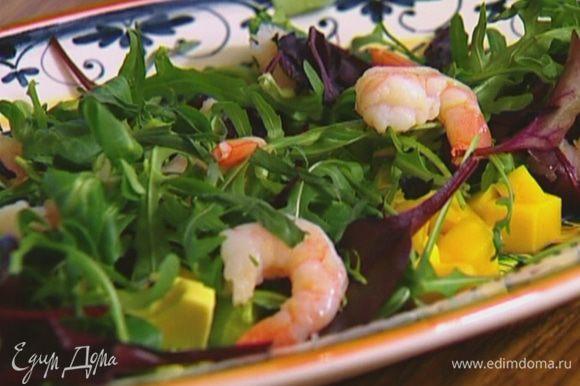 Манго и авокадо почистить, нарезать небольшими кубиками, выложить на блюдо, сверху разложить салатный микс, на него — креветки.