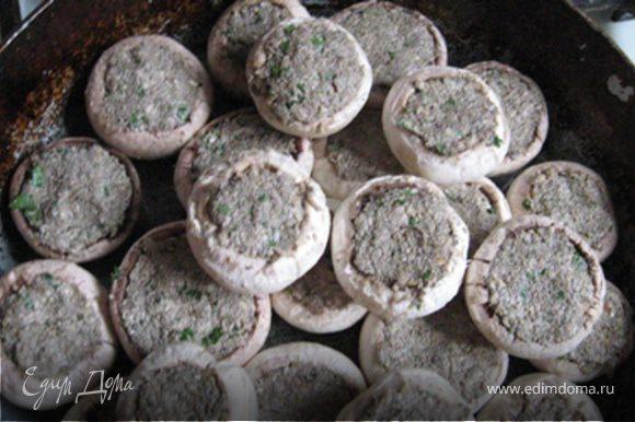 Смешать петрушку, сливки (или нежирную сметану), сыр, орехи с грибами и чесноком в однородную массу. Посолить, поперчить, добавить мускатный орех и нафаршировать шляпки. Предварительно их можно с двух сторон обжарить на сильном огне на масле, чтоб случилась у них корочка. Выложить грибы на противень и запекать в духовке 15 минут при 200 градусах.