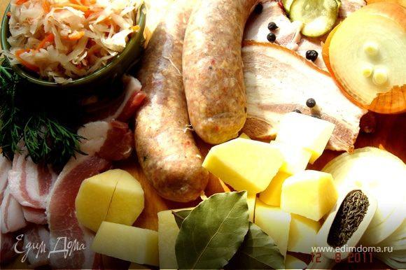 Кислую капусту промыть и обжарить с луком и морковью(если капуста с морковью,то дополнительно морковь можно не добавлять).Обжарить по отдельности колбаски,бекон и корейку,порезанную на куски.Картофель очистить и крупно порезать.В большую жаровню сложить картофель,капусту с луком и морковью,специи,посолить-поперчить и залить бульоном и,по желанию,вином.Довести до кипения и тушить на маленьком огне под крышкой ок.30 мин.Затем добавить мясо,бекон,порезанные колбаски и тушить ещё мин.20-30.Подавать с солениями,укропом,зелёным луком и свежим ржаным хлебом.Приятного аппетита!