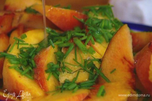 Персики, удалив косточки, нарезать дольками, посыпать шнитт-луком и полить лимонным соком.