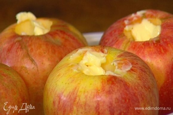 В выемку каждого яблока положить по 1 ч. ложке сливочного масла.