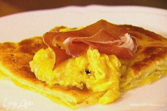 Вынуть из духовки готовые тосты из слоеного теста, выложить на каждый яичную начинку, а сверху кусочки ветчины.