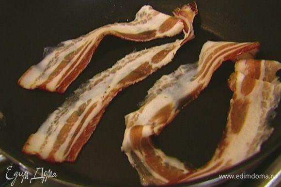 Бекон обжарить в разогретой сухой сковороде, затем выложить на бумажное полотенце, чтобы убрать излишки жира.