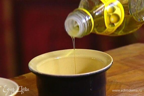 Две небольшие керамические формочки смазать оливковым маслом, посыпать дно и бока оставшимся сахаром и на 5 минут поставить в морозильник.