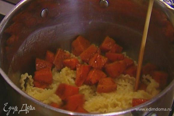 Вернуть макароны в кастрюлю, где они варились, добавить запеченную тыкву, перемешать.