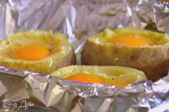В углубления в картофеле разбить по 1 яйцу и поставить противень в разогретую духовку на 5 минут.