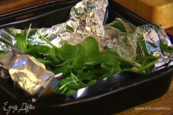 Форму для выпечки застелить фольгой, выложить листья шпината, так чтобы они покрыли все дно (немного листьев оставить).