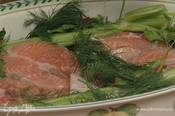 Филе семги уложить в жаропрочную посуду, туда же поместить стебли сельдерея, часть петрушки и укропа, нарезанный перец чили. Рыбу посолить, сбрызнуть лимонным соком и оставить на несколько минут мариноваться.