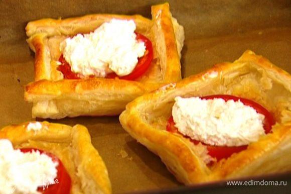 Вынуть из духовки противень с тестом, в центр каждого квадрата положить по кружку помидора, а сверху намазать козий сыр, так чтобы он полностью покрыл помидор.