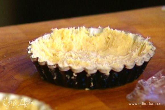 Охлажденное тесто разложить по формочкам, равномерно распределив по дну и бортикам.