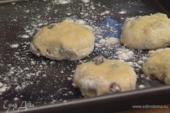 Присыпать противень мукой, выложить на него булочки и выпекать в разогретой духовке 25–30 минут.