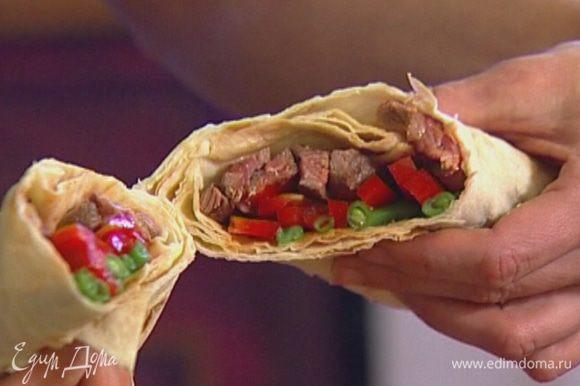 На лист лаваша выложить фасоль, сладкий перец, говядину и свернуть конвертиком, а затем разрезать наискосок пополам, чтобы получились два ролла.