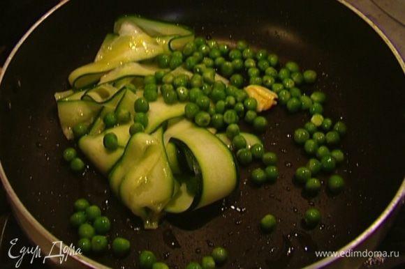 Выложить в сковороду полоски цукини, размороженный зеленый горошек и слегка прогреть.