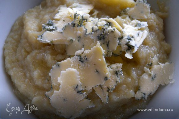 Измельчить все погружным блендером. Добавить половину сыра и перемешать. Разлить по тарелкам. Покрошить сверху оставшийся сыр и посыпать измельченной зеленью чеснока.