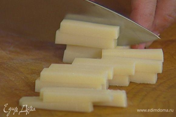 Сыр нарезать кусочками, выложить на салатные листья.