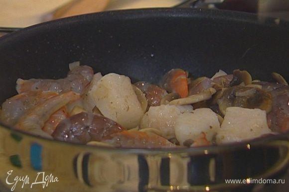 Рыбное филе нарезать на небольшие кусочки, выложить в сковороду к грибам, добавить размороженные креветки, посолить, поперчить, перемешать. Влить 2 ст. ложки вина, посыпать приправой к рыбе.