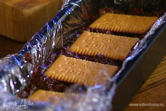 Небольшую форму выстелить пищевой пленкой, выложить шоколадную массу и украсить сверху целым печеньем.