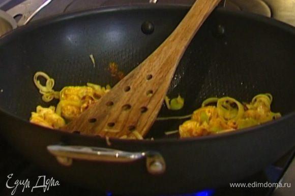 Разогреть в воке оливковое масло и обжаривать лук и чеснок 1 минуту, затем добавить куриное мясо и карри. Перемешать.