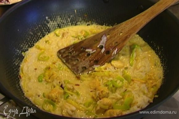 Добавить кокосовое молоко и 2 ст. ложки готового риса, перемешать и потомить 3–4 минуты.