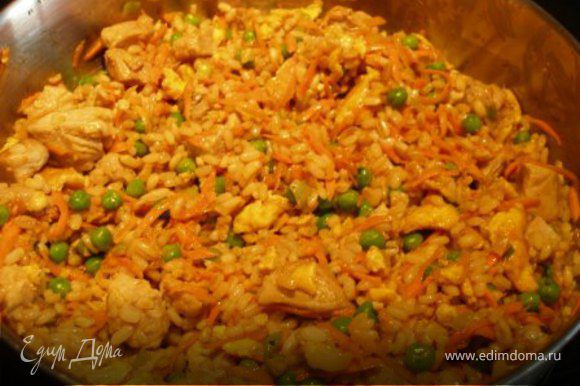 Добавить морковь, горошек, рис, жаренные яйца, соевый соус и уксус. Жарить 3 минуты, постоянно помешивая. Выключить огонь, накрыть крышкой и дать постоять несколько минут.