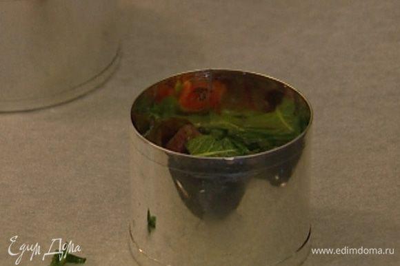 Выстелить противень бумагой для выпечки, разложить на нем круглые формочки-кольца без дна и наполнить каждую формочку салатом примерно до половины.