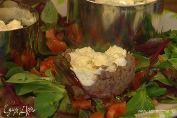 Оставшийся салат разложить на большом блюде, сверху поставить запеченные башенки из фасоли и сыра и снять кулинарные кольца.