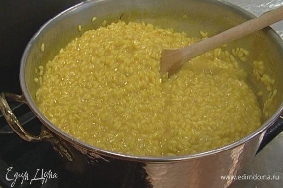 Влить вино и через 1 минуту начать добавлять бульон, половник за половником, позволяя рису впитывать жидкость.