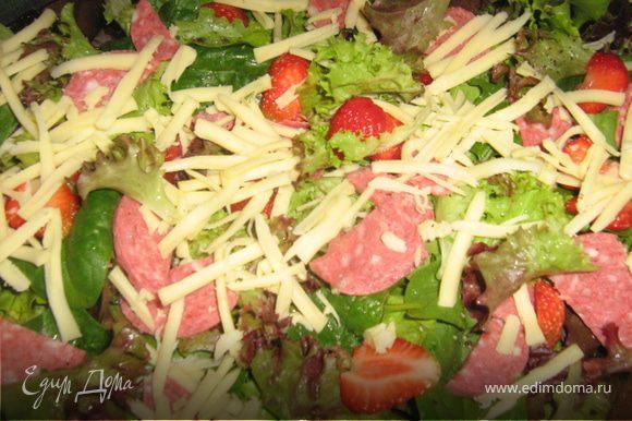Салями нарезать тонкими ломтиками. Сыр крупно натереть. Клубнику вымыть, высушить, нарезать пластинками. Выложить все на салат.