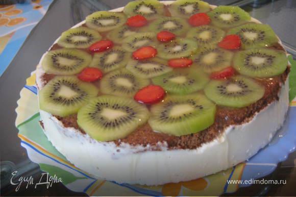 После полного застывания(около 1-2 часов) достаем торт из формы и приступаем к украшению.Киви очищаем и нарезаем кружочками,выкладываем на верхушку торта.Желе для торта готовим,согласно инструкции на упаковке на основе ананасового сока и выливаем на киви.Возвращаем торт в холодильник для застывания желе.