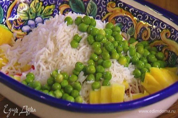 Добавить в салат вареный рис, зеленый горошек и кусочки курицы.