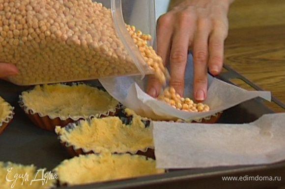 Из бумаги для выпечки вырезать квадраты по количеству и размеру тарталеток, выложить бумагу на тесто и насыпать сверху горох.