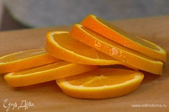 Апельсин нарезать кружками вместе с кожурой.