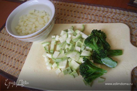 Нарежем картофель кубиками и замочим на 20-30 мин в воде. Нарежем кабачок кубиками. Порвем на более мелкие части веточки брокколи.