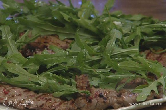Выложить мясо и руколу на блюдо, полить все заправкой и сразу подавать.